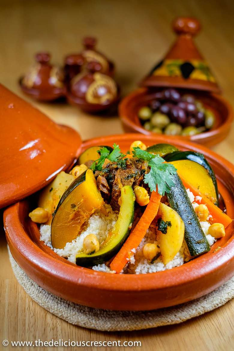 Couscous stew with vegetables in a tagin with olives in the background - for Ramadan 2021
