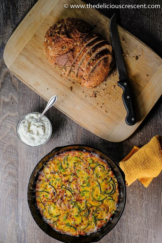 Persian zucchini kuku in a pan with bread load on a chopping board - for Ramadan 2021