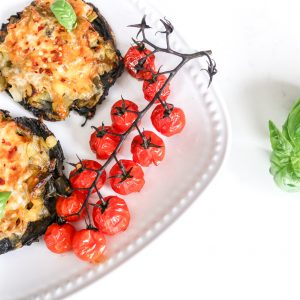 pizza made with portobello mushroom as a base with grilled tomatoes on a vine