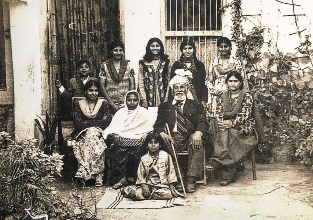 Black and white photo of an elder gentleman with a turban sitting with his family.