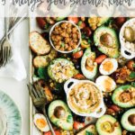 Sheet pan full of avocados, chickpeas, dips and bread