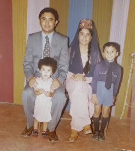 Dietitian, Shahzadi Devje, as a little girl posing for a family portrait with her parents and brother.