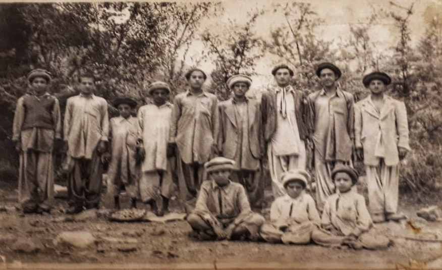 Black and white photo of men and boys in a rural village outdoors.