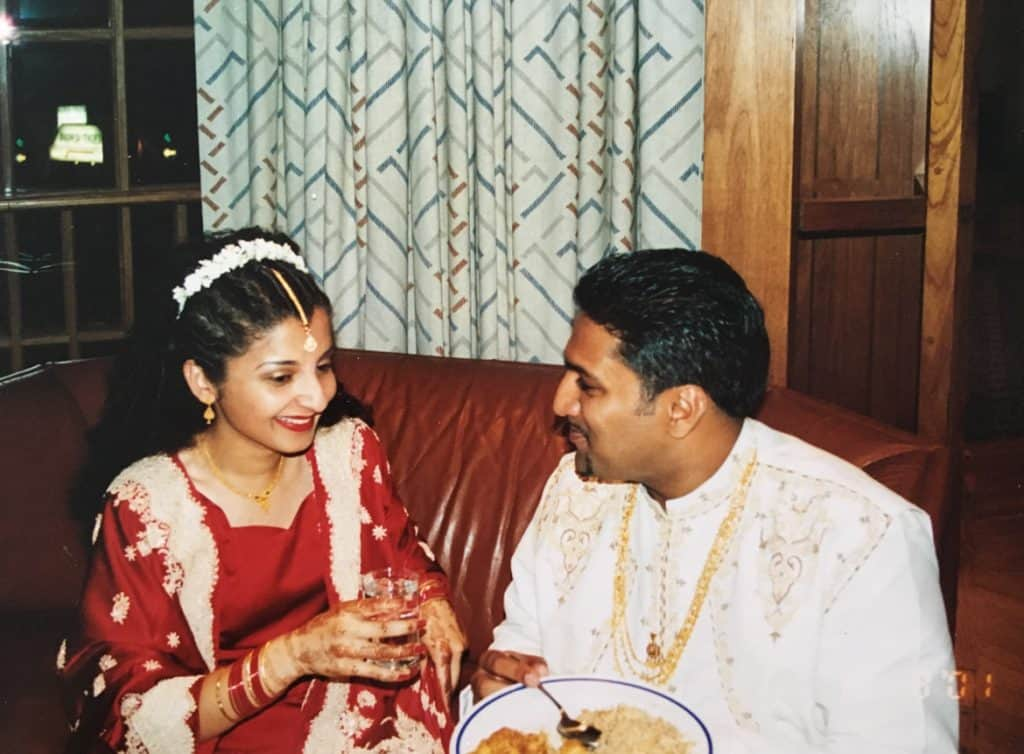 An Desi (South Asian) couple just married in their traditional outfits.