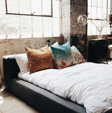 a bed with colourful pillows for sleeping