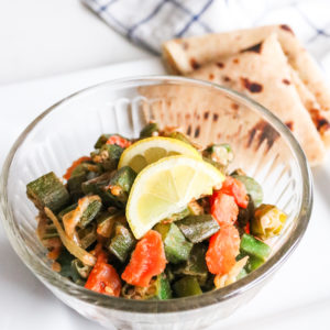 pkra (bhindi) in a bowl with roti and lemon slices