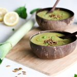 mint and pea soup served in 2 coconut bowls with leek and lemon on the side