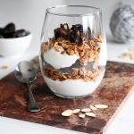 homemade granola parfait layered with yoghurt and dried prunes