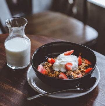 bowl of cereal with milk, yoghurt on a table