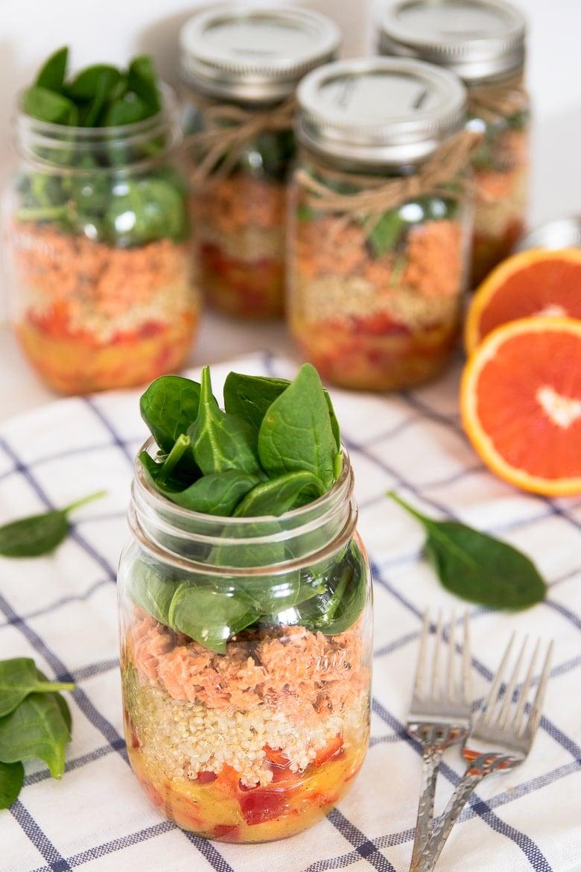 quinoa and salmon salad stored in five mason jars