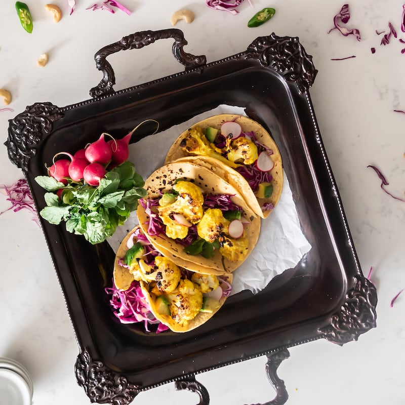 Tray with three corn cauliflower tacos with purple cabbage and avocado cubes