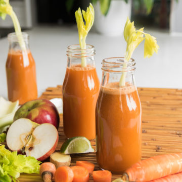 bottles of homemade carrot juice with raw ingredients around the three bottles