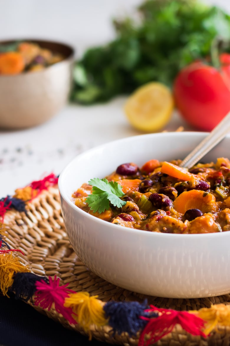 2 bowls of superfood vegetarian chili on a traditional Pakistani straw basket with herbs and tomatoes