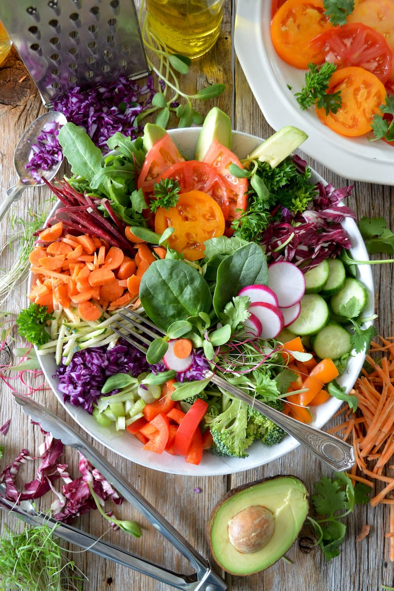 bowl of different variety of colorful raw vegetables with a fork
