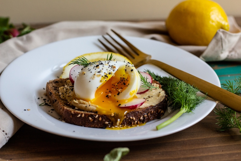 plate with egg on toast with hummus spread