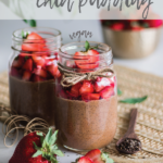 two jars of chocolate chia pudding topped with fresh strawberries with strawberries around