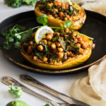 Chickpea Kale Curry Stuffed Spaghetti Squash boats on a baking tray garnished with lemon slice and fresh cilantro