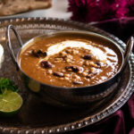 daal makhani in a silver bowl on a round tray on top of a maroon velvet cloth with maroon flowers and roti in the background