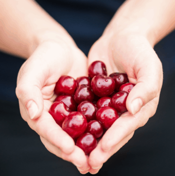 a person holding a handful of cherries in the shape of a heart