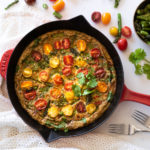 Asparagus Frittata topped with colorful tomatoes in a red pan on a table cloth