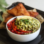bowl of pigeon peas coconut curry (bharazi) with red roasted pappers and lemon segments on a tray with mandazi (coconut bread)