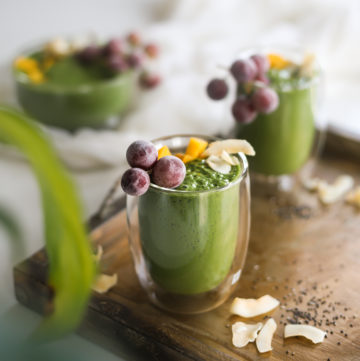 green smoothie glasses in a tray topped with frozen grapes, mango segments and coconuts flakes