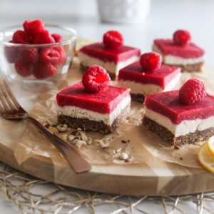 five raspberry vegan bars with a raspberry on each slice, placed on a wooden board with sprinkle of chopped nuts and a gold fork