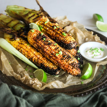 pile of bbq corn coated in spices on a tray with lime segments and dipping sauce