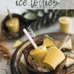 Pineapple Coconut Ice Lollies in a coconut shell on a bed of ice in a tray with a spoon of turmeric and sliced pineapples around