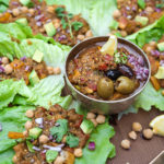 lettuce leaves filled with baingan bharta (Indian eggplant recipe) with 2 bowls of baingan bharta next to them.