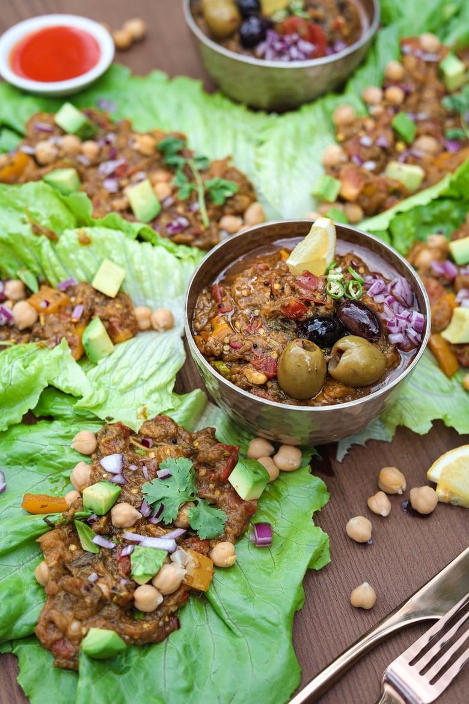 lettuce leaves filled with baingan bharta (Indian eggplant recipe) with 2 bowls of baingan bharta next to them.