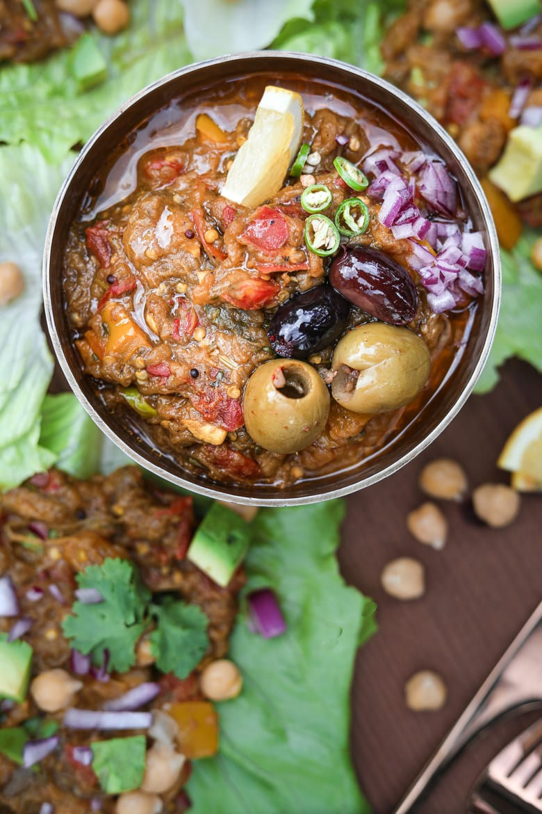 a bowl of baingan bharta topped with olives and chilli with lettuce leaves filled with baingan bharta (Indian eggplant recipe) withlettuce leaves filled with baingan bharta (Indian eggplant recipe) with lettuce leaves filled with bharta in the background