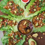 lettuce leaves filled with baingan bharta (Indian eggplant recipe) with a bowl of baingan bharta in the center.