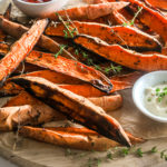 pile of baked sweet potato wedges on a wooden round board with two bowls of dipping sauces