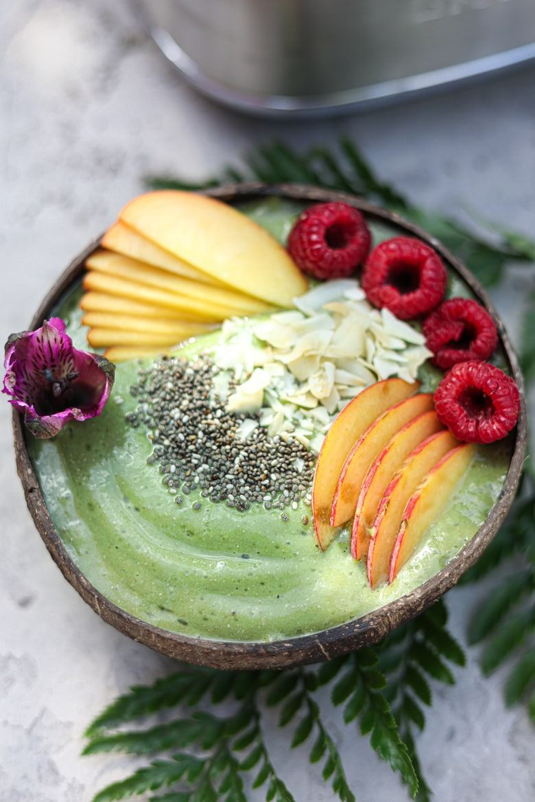 healthy green smoothie bowl topped with sliced peaches, raspberries, coconut and chia seeds