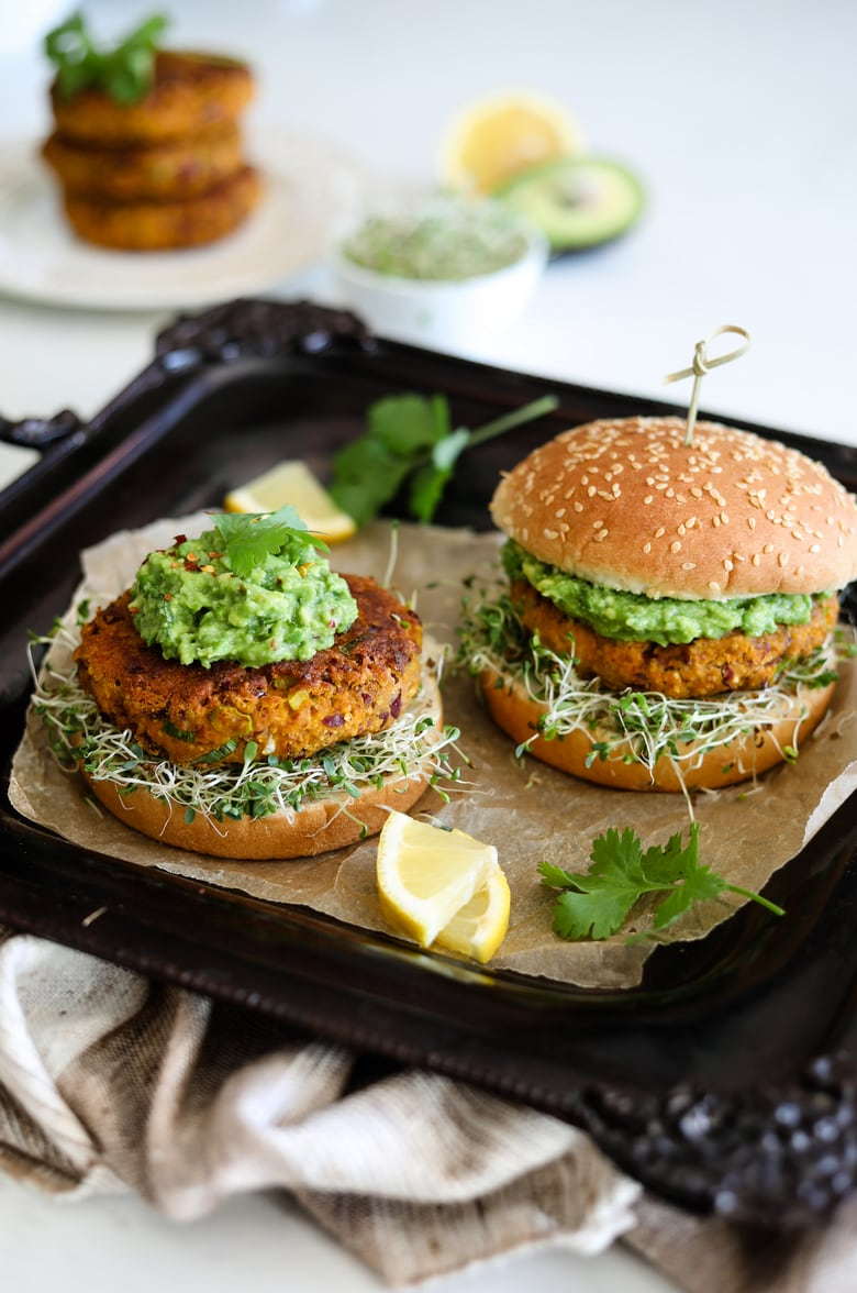 Two Desi Pumpkin Bean Burgers on a bed of alfalfa microgreens topped with guacamole in burger buns on a black tray