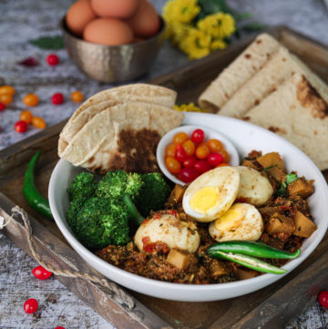 Egg curry recipe with turnips in a bowl with roti, broccoli, and tomatoes in a gold tray