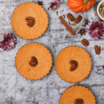 a row of homemade pumpkin pies topped with pecans with pumpkins and flowers in the background