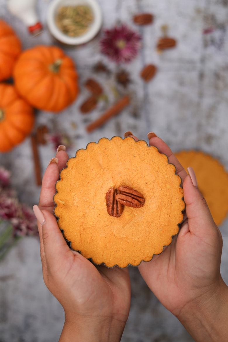 hands holding a homemade pumpkin pies topped with pecans with pumpkins and spices in the background