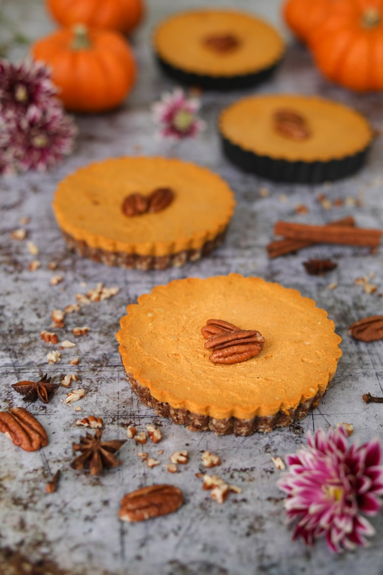 a row of homemade pumpkin pies topped with pecans with pumpkins in the background