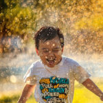 a happy child running in a splash of water on a sunny day