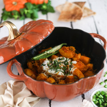 Afghan pumpkin curry in a pumpkin cocotte surrounded by fresh pumpkins, herbs and naan bread