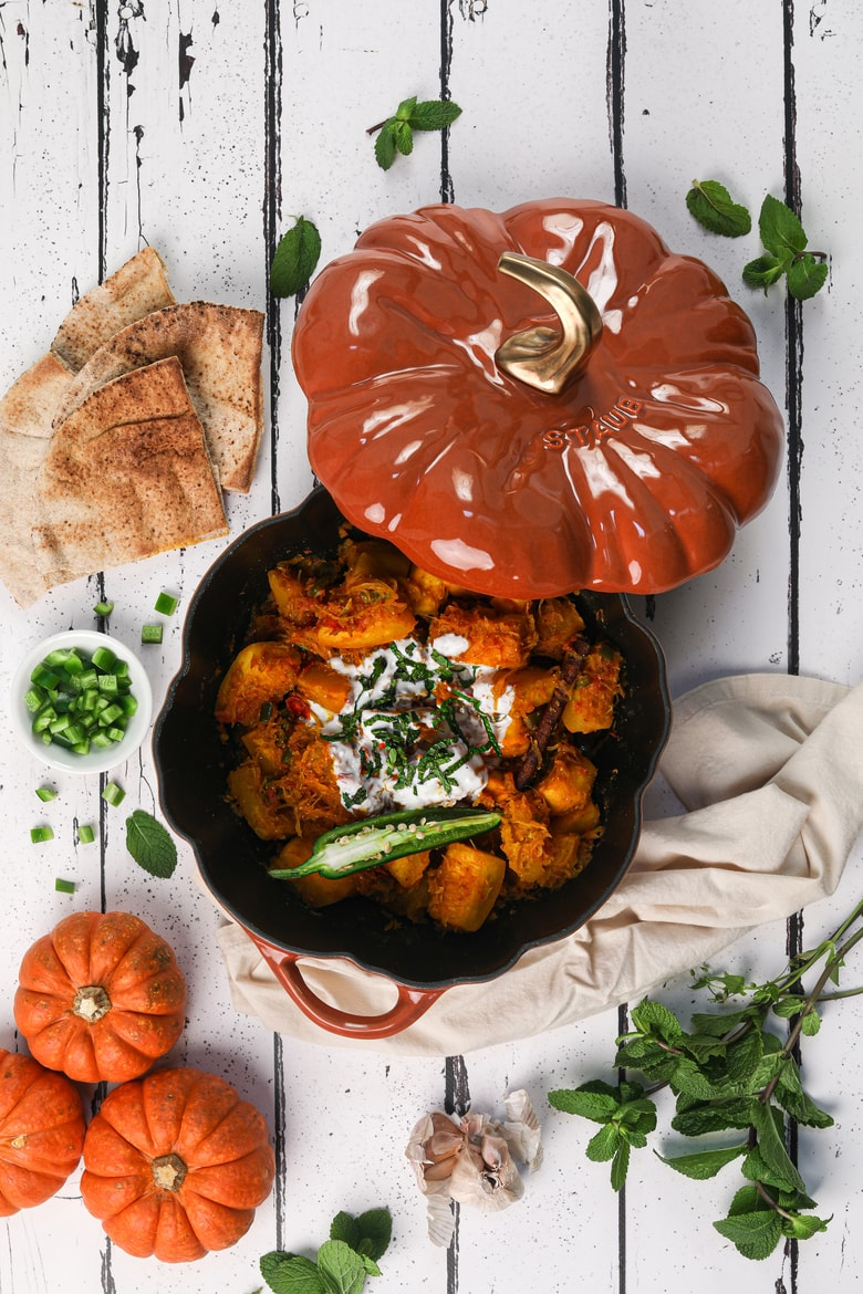 flat lay image of Afghan pumpkin curry in a pumpkin cocotte surrounded by fresh pumpkins, herbs and naan bread