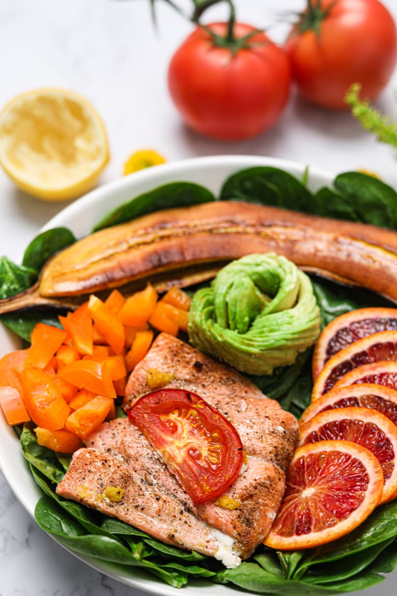 Lemon Pepper Salmon fillet served Buddha bowl style on a bed of spinach with peppers, avocado, orange segments and grilled plantain