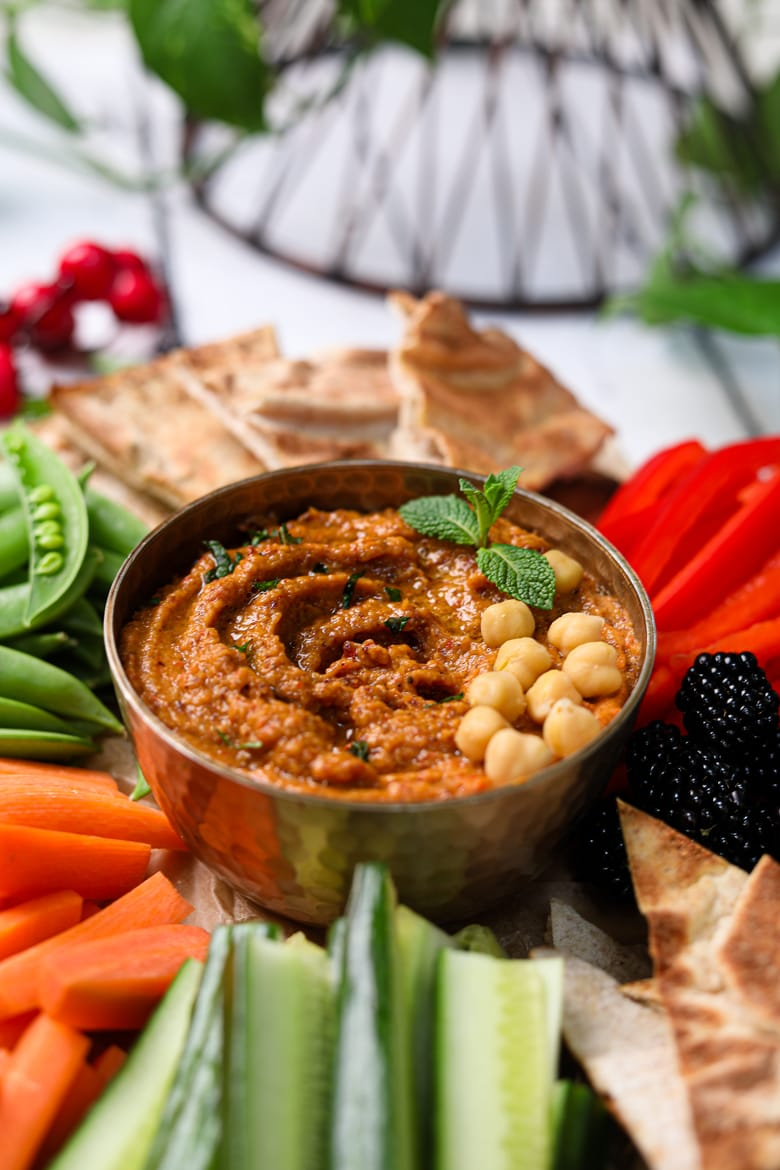 Holiday veggie dip with chcikpeas on top surrounded by fruits and vegetables