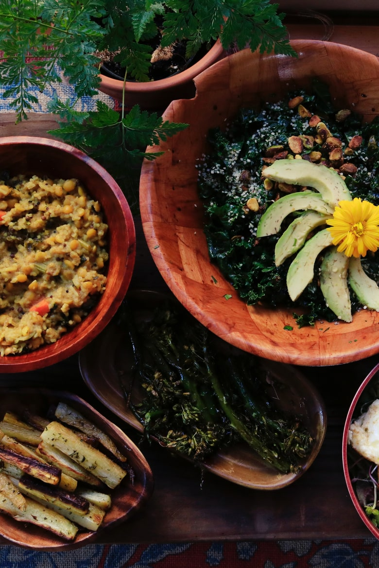 bowls and plates of food with avocado slices, lentils and a green plant