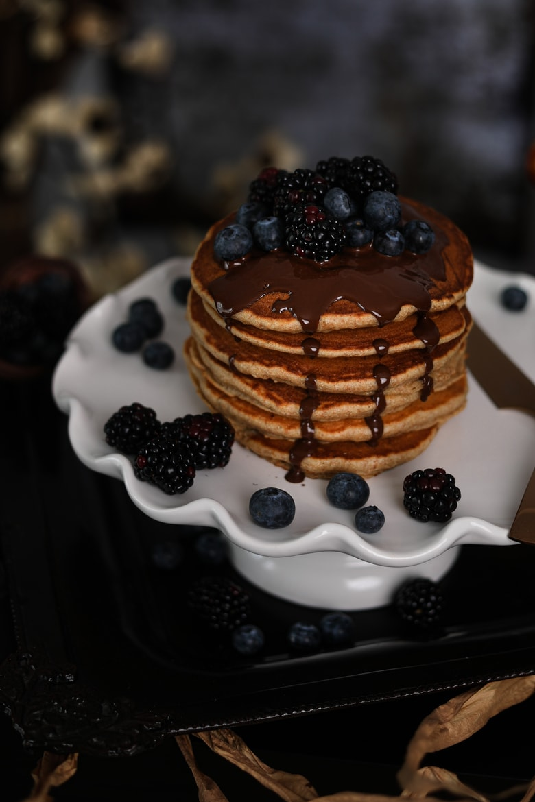stack of fluffy pancakes on a cake stand topped with blackberries and blueberries and dark chocolate with flowers in the background