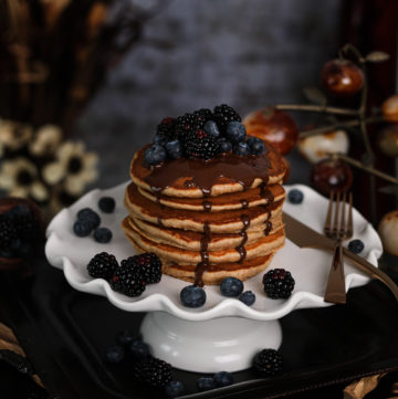 stack of fluffy pancakes on a cake stand topped with blackberries and blueberries and dark chocolate with flowers and decorations all around