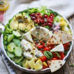 bowl full of salad topped with avocado, cucumber, tomatoes, cheese and naan bread