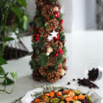 Plate of easy and healthy roasted Brussel sprouts recipe with sweet potatoes and cranberries with a Christmas tree in the background